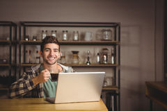 Smiling hipster drinking coffee and using laptop Stock Photography