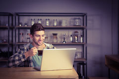 Smiling hipster drinking coffee and using laptop Stock Images