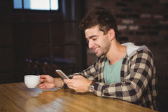 Smiling hipster drinking coffee and using smartphone Royalty Free Stock Images