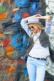 Smiling hipster girl against urban wall Stock Photography
