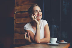 Smiling hipster girl calling with cell telephone while relaxing after walking in summer day stock photography
