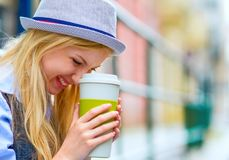 Hipster girl with cup of hot beverage on city street Royalty Free Stock Photos