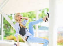 Smiling hipster girl having fun while sitting on urban structure Stock Image