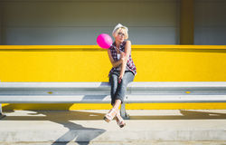 Smiling hipster girl posing with pink balloon at parking lot Stock Photos
