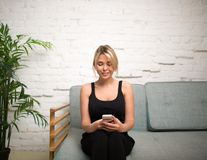 Smiling hipster girl reading e-mail on portable cell telephone, sitting on couch in home Stock Photos