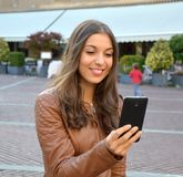 Smiling hipster girl is reading pleasant text message from her friend on mobile phone outdoor.  Royalty Free Stock Images