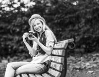 Hipster girl with retro photo camera sitting on bench in royalty free stock photo
