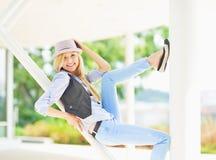 Smiling hipster girl sitting on urban structure. Smiling hipster girl in hat sitting on urban structure Royalty Free Stock Image