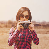 Smiling hipster girl takes photographs with vintage photo camera Stock Photos
