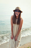 Smiling hipster girl walking on a sea beach. Royalty Free Stock Images