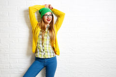 Smiling Hipster Girl at White Brick Wall Background. Street Syle. Trendy Casual Fashion Outfit in Spring or Autumn. Copy Space Royalty Free Stock Photo