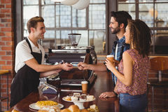 Smiling hipster giving credit card to barista. At coffee shop Stock Photos