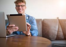 Smiling hipster guy having video call in social network via portable touch pad Royalty Free Stock Photography