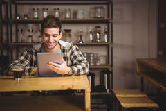 Smiling hipster having coffee and using tablet computer Stock Image