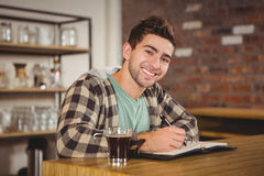 Smiling hipster having coffee and writing in planner Royalty Free Stock Images