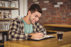 Smiling hipster having coffee and writing in planner Stock Photography