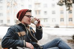 Smiling hipster man drink coffee outdoor. Smiling hipster man in a hat drink coffee outdoor royalty free stock images