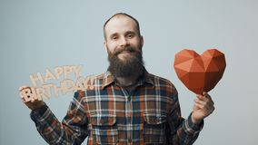 Hipster man showing and giving you a Happy Birthday text. Smiling hipster man holding heart shape and showing a Happy Birthday text stock video