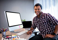 Smiling hipster man posing for camera at computer desk in studio Royalty Free Stock Images