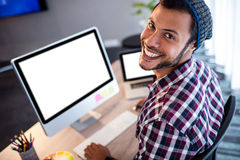 Smiling hipster man posing for camera while sitting at computer desk Royalty Free Stock Image