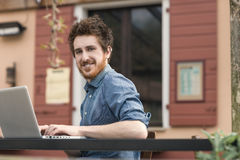 Smiling hipster man using a laptop outdoors Royalty Free Stock Photo