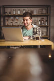 Smiling hipster sitting and using laptop Stock Images