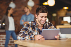 Smiling hipster sitting and using tablet computer Royalty Free Stock Photo