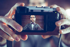 Smiling hipster taking self portrait through camera Stock Photos