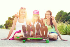 Smiling hipster teenage friends with skateboard, colorised image with sunflare Royalty Free Stock Photo