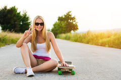 Smiling hipster teenage girl with skateboard, image with sunflare Stock Photos
