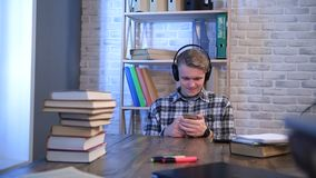 Smiling hipster using smartphone to listen music stock footage