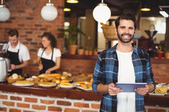 Smiling hipster using tablet in front of working barista Royalty Free Stock Photos
