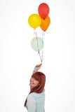 Smiling hipster woman holding balloons. Against white background Royalty Free Stock Photography