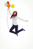 Smiling hipster woman holding balloons. Against white background Royalty Free Stock Image