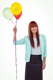 Smiling hipster woman holding balloons. Against white background Royalty Free Stock Images