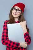 Smiling hipster woman holding laptop computer. Portrait of a smiling hipster woman holding laptop computer over gray background and looking at camera Royalty Free Stock Photography