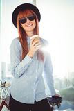 Smiling hipster woman leaning on a bike Stock Photography