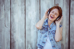 smiling hipster woman listening to loud music through headphones Stock Photo