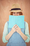 smiling hipster woman looking out over a book Royalty Free Stock Photography