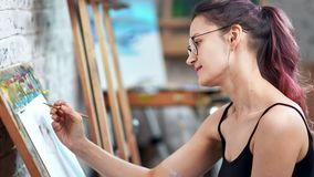 Smiling hipster woman painter making graphic illustration on white paper sheet medium close-up. Focused female artist enjoying working drawing sketch at art stock footage
