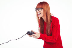 Smiling hipster woman playing video games. Against white background Royalty Free Stock Photography