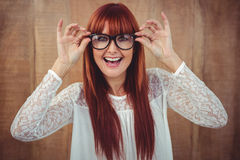Smiling hipster woman posing face to the camera. Against wooden background Stock Image
