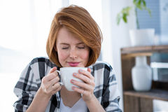 smiling hipster woman smelling a cup of coffee Stock Photos