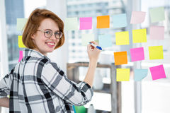Smiling hipster woman sticking notes on a notice board Stock Photography