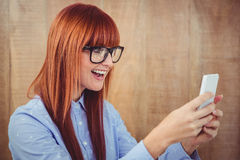 Smiling hipster woman texting on her smartphone Stock Image