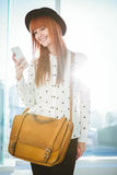 Smiling hipster woman texting with her smartphone Stock Photos