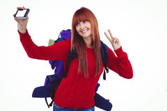 Smiling hipster woman with a travel bag taking selfie. Against white background Stock Photography