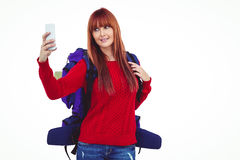 Smiling hipster woman with a travel bag taking selfie. Against white background Stock Image