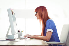Smiling hipster woman typing on keyboard Stock Photos