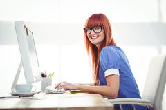 Smiling hipster woman typing on keyboard Stock Images